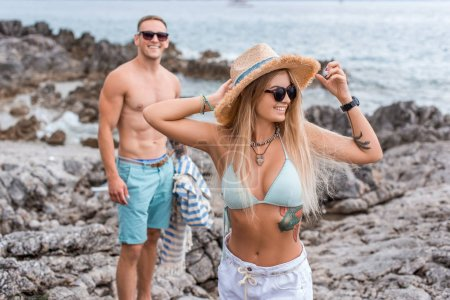 Photo for Girlfriend in bikini top touching straw hat at beach in Montenegro - Royalty Free Image