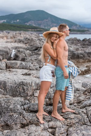 cheerful girlfriend and boyfriend standing together on rocky beach in Montenegro