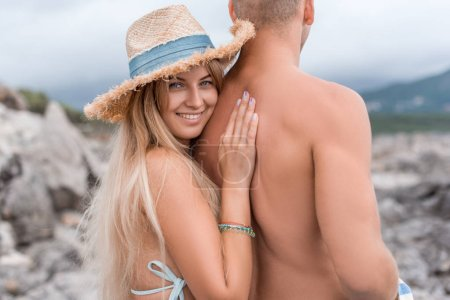 Photo for Smiling girlfriend touching shirtless boyfriend at beach in Montenegro - Royalty Free Image