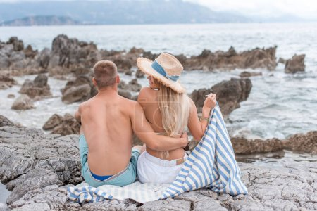 rear view of girlfriend and boyfriend sitting on rocky beach of adriatic sea in Montenegro