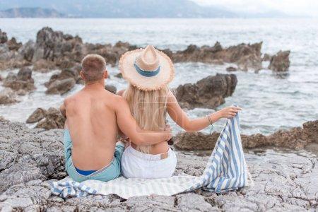 back view of girlfriend and boyfriend sitting on rocky beach in Montenegro