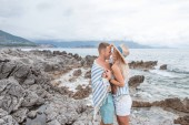side view of beautiful happy young couple in love hugging and smiling each other on rocky beach in montenegro