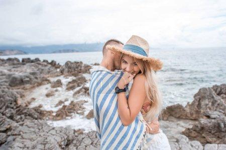 young man hugging beautiful smiling girlfriend on rocky beach in montenegro