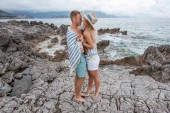 side view of beautiful young couple standing together and hugging on rocky beach in montenegro