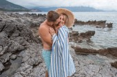 muscular shirtless man hugging and kissing beautiful happy young girlfriend on rocky beach in montenegro