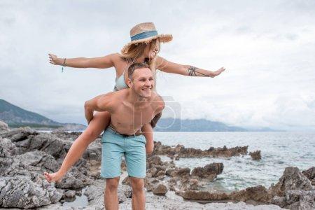 Photo pour Heureux jeune couple ferroutage sur une plage rocheuse au Monténégro - image libre de droit