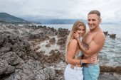 side view of beautiful happy young couple hugging and smiling at camera on rocky beach in montenegro