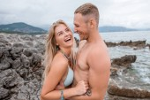 side view of happy young couple hugging and laughing on rocky beach in montenegro