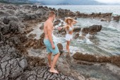 beautiful happy young couple holding hands on rocky beach in montenegro