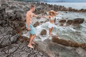 happy young couple holding hands and smiling each other on rocky beach in montenegro
