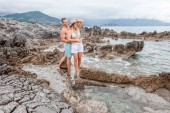 happy young couple embracing and looking away while standing together on rocky beach in montenegro