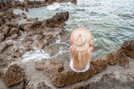high angle view of young woman in straw hat sitting on rocky beach in montenegro