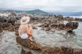girl in bikini top and straw hat sitting on rocky beach in montenegro