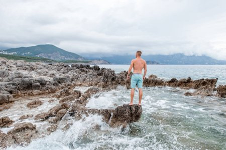 back view of handsome muscular young man standing on rocky beach and looking at majestic sea view in montenegro