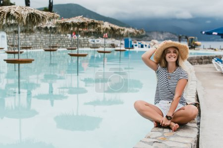 beautiful happy young woman in straw hat sitting near pool and smiling at camera, montenegro