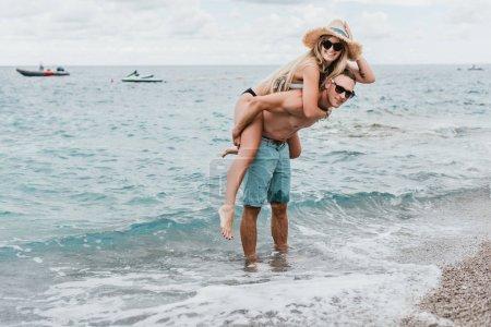 Photo pour Heureux couple jeune à lunette de ferroutage sur la plage au Monténégro - image libre de droit