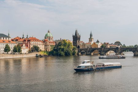 PRAGUE, CZECH REPUBLIC - JULY 23, 2018: famous charles bridge and boats on Vltava river in prague, czech republic