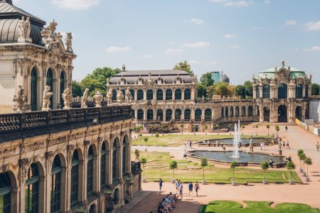 DRESDEN, GERMANY - JULY 24, 2018: tourists walking near fountains and beautiful architecture of ancient Zwinger palace in Dresden, Germany