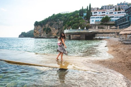 woman walking from pier to ricardova glava beach in Budva, Montenegro