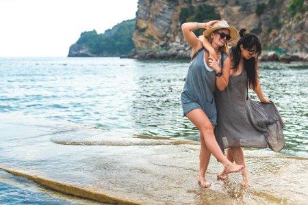 Foto de Mujeres atractivas abrazos y la diversión en el muelle en Playa Ricardova Glava, Budva, Montenegro - Imagen libre de derechos