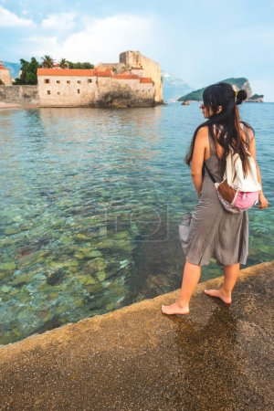 Photo for Woman standing on pier with Stari Grad (Old Town) on background in Budva, Montenegro - Royalty Free Image