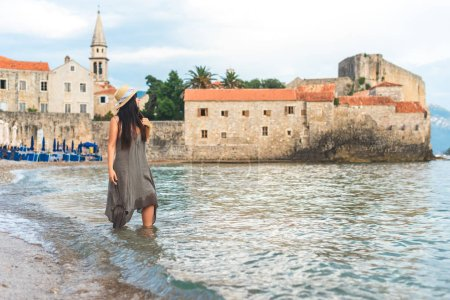 woman standing in Adriatic sea with Bell Tower of Sveti Ivana Cathedral on background in Budva, Montenegro