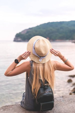 back view of woman holding hat and looking at Adriatic sea at Ricardova Glava beach, Budva, Montenegro