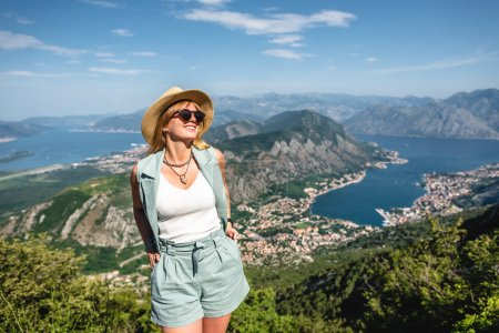 happy woman standing with Kotor bay and Kotor town on background in Montenegro