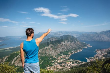 Photo for Back view of man reaching out hand for Kotor bay and Kotor town in Montenegro - Royalty Free Image