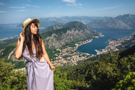 beautiful woman posing with Kotor bay and Kotor town on background in Montenegro