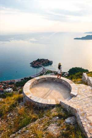 high angle view of woman standing on viewpoint near saint stephen island in Adriatic sea, Budva, Montenegro