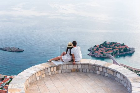couple hugging on viewpoint and looking at island of Sveti Stefan in Budva, Montenegro