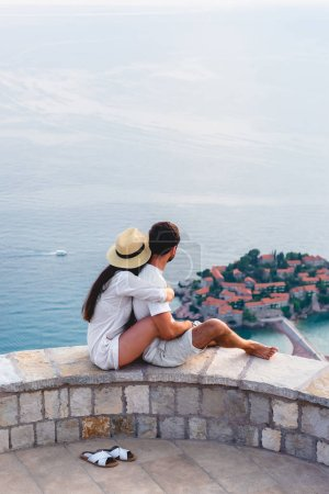 couple hugging and looking at island of Sveti Stefan in Adriatic sea, Budva, Montenegro