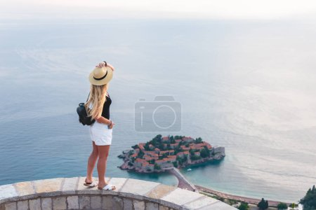 woman standing and looking at saint stephen island in Adriatic sea, Budva, Montenegro
