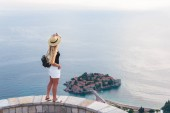 woman standing and looking at saint stephen island in Adriatic sea, Budva, Montenegro