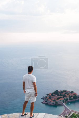 back view of man looking at island of Sveti Stefan with hotel resort in Adriatic sea, Budva, Montenegro