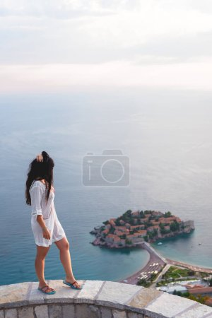 side view of woman looking at island of Sveti Stefan with hotel resort in Adriatic sea, Budva, Montenegro