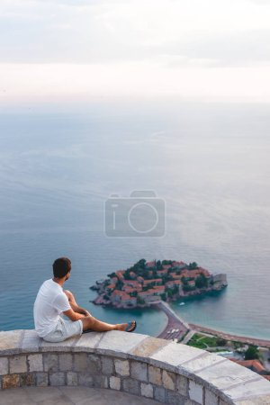 Photo for Man sitting on viewpoint and looking at island of Sveti Stefan with hotel resort in Adriatic sea, Budva, Montenegro - Royalty Free Image