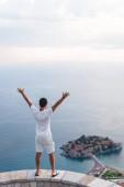 """Постер, картина, фотообои """"вернуться мнение человека с поднятыми руками, глядя на острове Свети-Стефан с курортный отель в Адриатическом море, Будва, Черногория"""""""