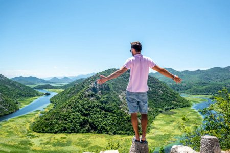 back view of man in pink shirt standing on stone of viewpoint near Crnojevica River in Montenegro