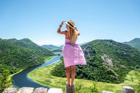 back view of woman in pink dress standing on stone of viewpoint near Crnojevica River in Montenegro