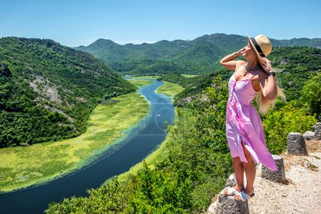 attractive woman in pink dress standing on stone of viewpoint near Crnojevica River in Montenegro