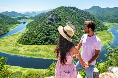Photo pour Couple en vêtements roses, tenant par la main et en regardant la rivière Crnojevica au Monténégro - image libre de droit
