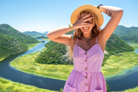 woman in pink dress and hat looking at camera through fingers near Crnojevica River in Montenegro