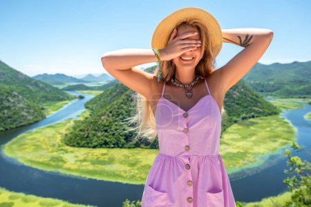 smiling woman in pink dress and hat covering eyes near Crnojevica River (Rijeka Crnojevica) in Montenegro