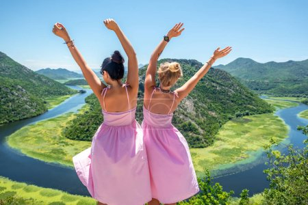 back view of women in pink dresses standing with raised hands near Crnojevica River (Rijeka Crnojevica) in Montenegro