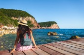 back view of woman with backpack sitting on bridge near sea in Budva, Montenegro