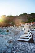 empty sun loungers on beach of adriatic sea with sunlight in Budva, Montenegro
