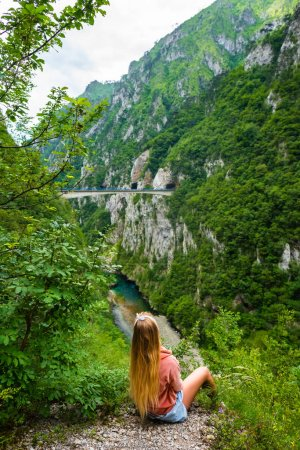 back view of woman looking at bridge between mountains above Piva River in Piva Canyon in Montenegro