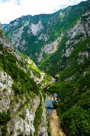 aerial view of bridge between mountains and house in Piva Canyon in Montenegro